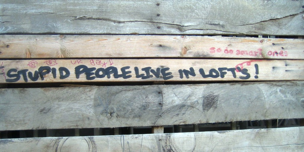 "Wood hoarding with graffiti ""Stupid people live in lofts""."